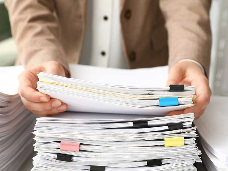 Business person with a large pile of papers with bulldog clips